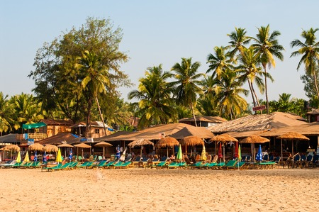 Palm trees and reed huts on a beach at sunset, Goa, India Stock Photo