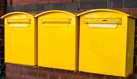 mail slot: Three yellow mail-boxes on brick