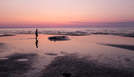 jurmala: Sunset on the beach and silhouette of man, Jurmala Stock Photo