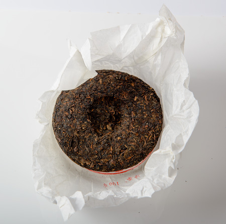 unwrapped: chinese puer tea cake in unwrapped packing on white background Stock Photo