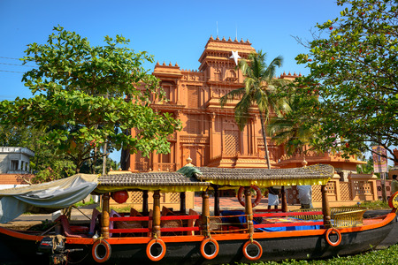 alappuzha: Traditional Indian boat with historic building at background in Allepey, Kerala
