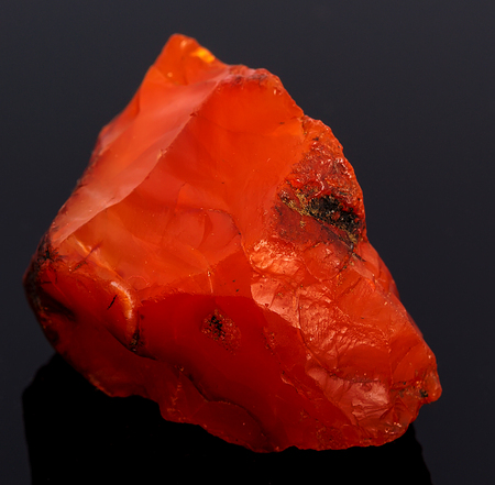 carnelian: Rough red carnelian gem isolated on black background
