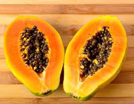 two pieces: Sliced fresh papaya in two pieces on wooden background