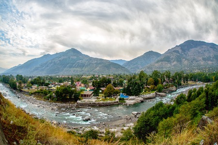 Village in Kullu Valley with Beas river in foreground, India Stock Photo