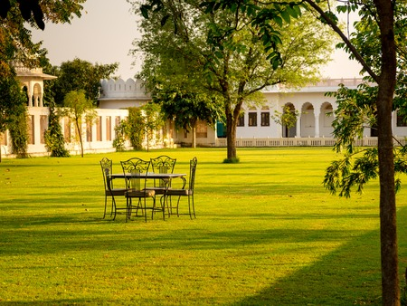 maharaja: Table with chairs ready for breakfast  under tree in the morning. Talabgaon castle heritage hotel, maharaja style, India