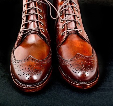 edmonds: Wingtip dark chili brown dress boots isolated on black background Stock Photo