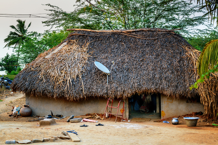 Traditional thatch hut with satellite TV dish