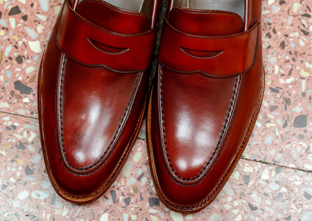 Pair of leather cherry calf penny loafer shoes on the stone floor together one by one closely. Close up