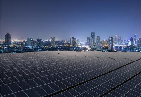 太陽電池パネル、夕暮れの街並みと太陽ファーム 写真素材