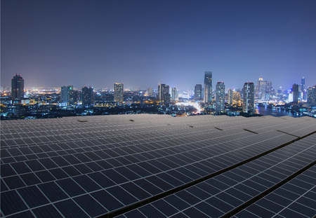 Solar panel,Solar farm with twilight cityscape Imagens
