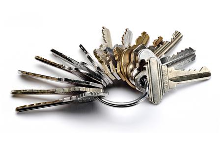 Sluit omhoog van metaalsleutelring met vele versleten die sleutels op wit worden geïsoleerd