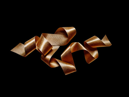 Close up of gold bronze metallic ribbon isolated on black background