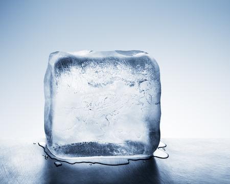 Bloco de gelo gelado, translúcido, azul, derretendo para criar uma poça de água na superfície de aço riscada Foto de archivo - 90469746