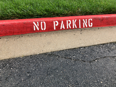 Red no parking road side curb sign with green grass and asphalt