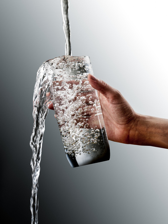 Female hand with overflowing glass of water on grey gradation Foto de archivo