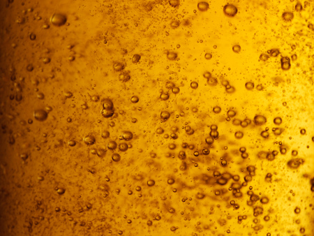 Abstract closeup of freshly poured amber gold beer with carbonation bubbles