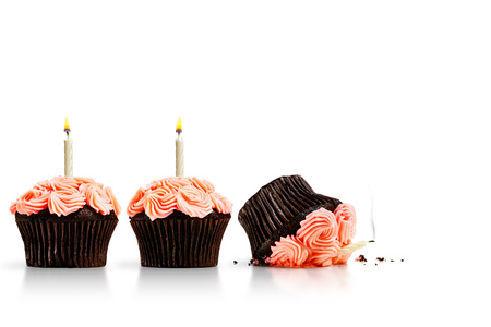 Smashed cupcake in row of cupcakes with candles isolated on white Фото со стока