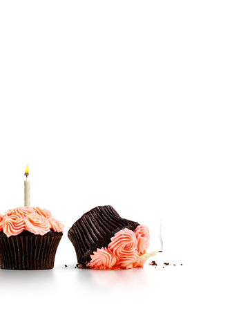 Smashed cupcake in row of cupcakes with candles isolated on white Stok Fotoğraf