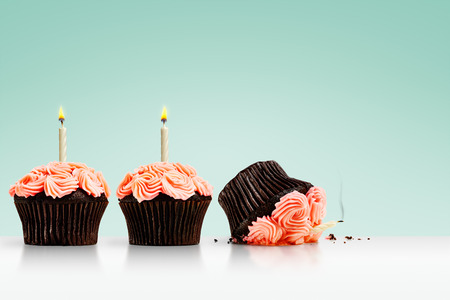 Smashed cupcake in row of cupcakes with candles on green background