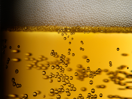 Closeup of freshly poured golden amber beer with frothy head and bubbles in a glass