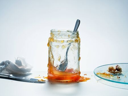 Messy, almost empty jar of homemade apricot preserves with spoon and knife beside plate with biscuit crumbs on cool white table Foto de archivo