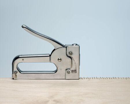 Der silberne Metallhefter erzeugt eine präzise Reihe von Heftklammern in heller Holzoberfläche mit blauem Hintergrund. Konzeptbesessenheit, Zwang, sich wiederholend.