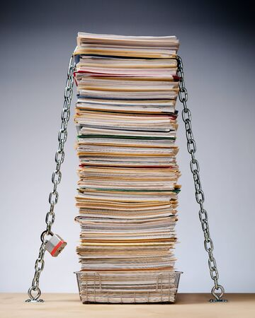 Data security conceptual image of desk with a tall stack of files and paperwork protected by padlock and chain