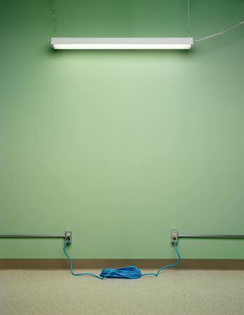 Dangerous electrical circuit, created by blue coiled extension cord plugged into two AC wall outlets with flourescent light on green wall Banco de Imagens