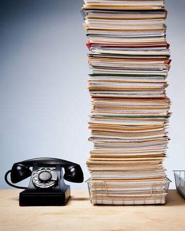 Vecchio telefono sulla scrivania con un'alta pila di file e scartoffie Archivio Fotografico