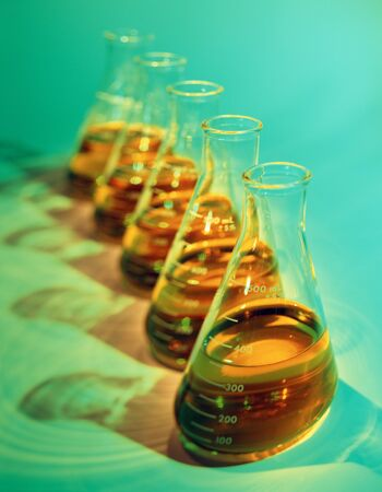 Illustrative, wide angle, selective focus image of row of chemical flasks with bright yellow toxic looking solutions on green background.