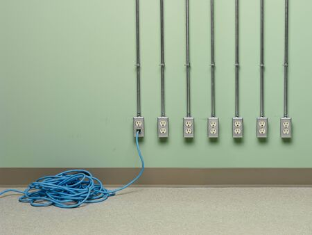 Blue coiled electric extension cord plugged into choice of AC outlets on green wall. Banco de Imagens