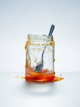 Messy, almost empty jar of homemade apricot preserves with spoon and spilled jam on cool white background