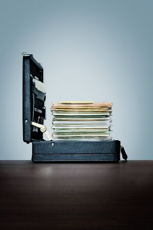 Compusive overwork, workaholic. Stack of files and folders in briefcase. on dark wood desk with blue background
