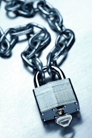 Security concept showing high strength steel padlock and chain with key on scratched steel surface