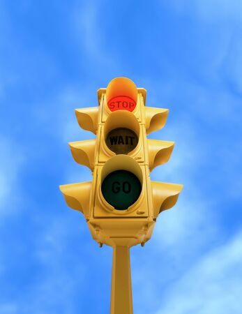Upward view of  tall vintage yellow traffic light with red STOP signal on blue sky background Banco de Imagens