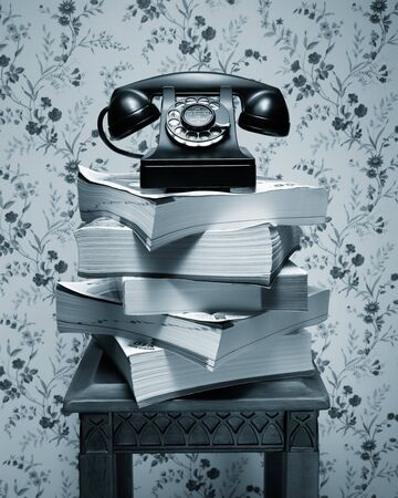 Vintage antique black rotary dial telephone standing on stack of phone books and wooden table