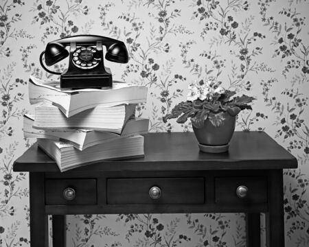 Vintage antique black rotary dial telephone standing on stack of phone books and wooden table with plant Banco de Imagens - 128872620