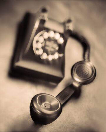 Old black bakelite dial telephone on rustic metal surface. Selective focus, sepia tone Banco de Imagens