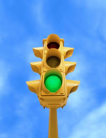 Upward view of tall vintage yellow traffic signal with green light on blue sky background Banco de Imagens