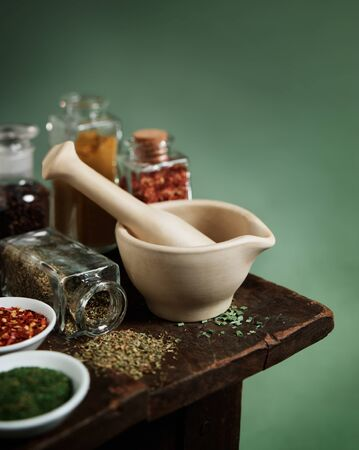 Vintage mortar and pestle with spices and herbs on wooden table Reklamní fotografie