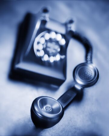 Old black bakelite dial telephone on rustic metal surface. Selective focus, black and white Banco de Imagens - 128872642