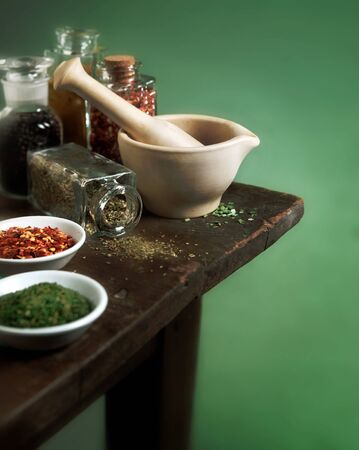 Vintage mortar and pestle with spices and herbs on wooden table Banco de Imagens