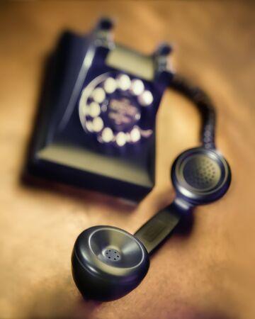 Old black bakelite dial telephone on rustic metal surface. Selective focus