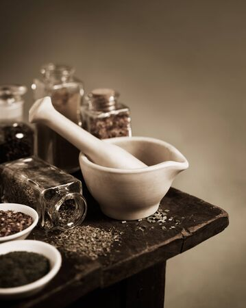 Vintage sepia toned mortar and pestle with spices and herbs on wooden table Banco de Imagens