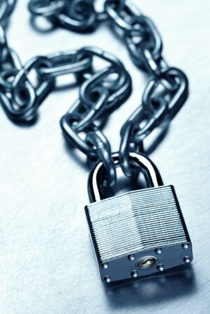 Security concept showing tough strong steel padlock and chain on scratched steel surface Reklamní fotografie