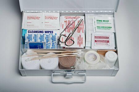 Kit di pronto soccorso organizzato imballato con forniture mediche di emergenza su sfondo grigio