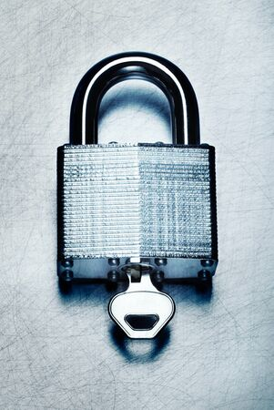 High security steel padlock with key on scratched steel surface.