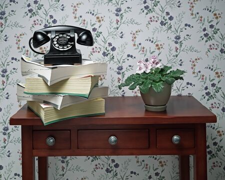 Vintage antique black rotary dial telephone standing on stack of phone books and wooden table with plant Banco de Imagens