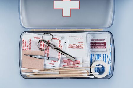 Organized first aid kit packed with emergency medical supplies on grey background