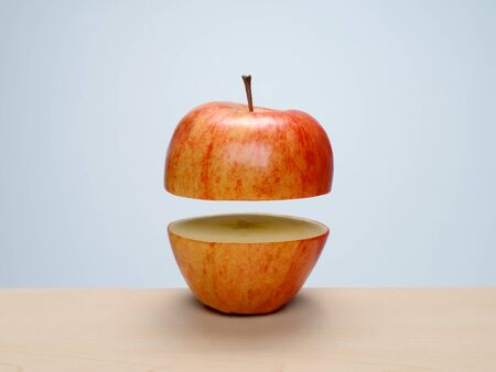 Ripe red apple cut in half, separated and floating apart. Concept: parts, apart, float, levitate, separation